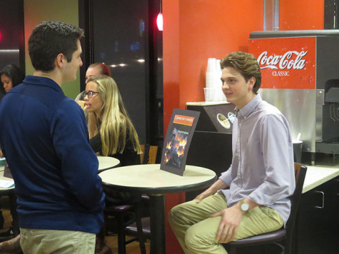 """Cameron Webb, senior, discusses his short story, """"Roommates,"""" with Andrew Parasch, senior. The Creative Writing book release party was held at North Cafe on Dec. 1."""