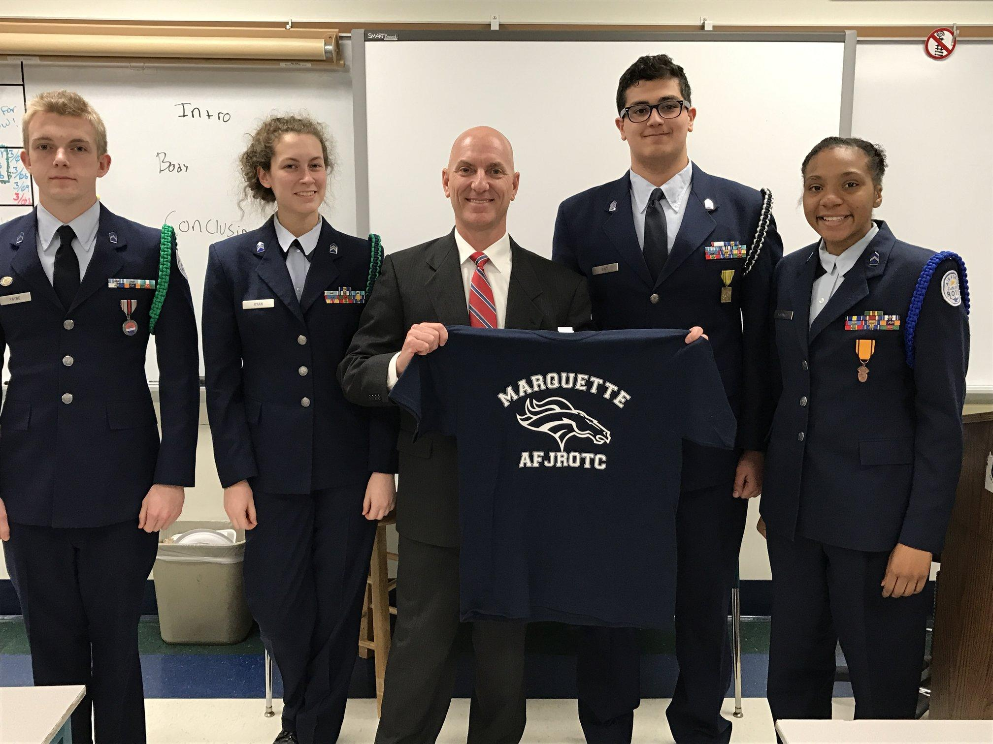 Inspector (Col-Ret) Todd Taylor and the Presentation Team hold up a MHS AFJROTC shirt.