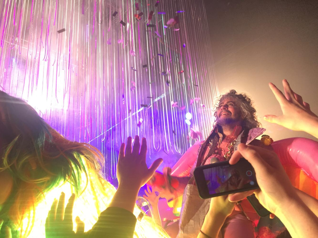 Wayne+Coyne%2C+lead+singer+of+the+Flaming+Lips%2C+passes+through+the+crowd+on+a+neon+unicorn+during+the+song+%22There+Should+be+Unicorns.%22+Coyne+utilized+neon+lights+and++inflatable+objects+to+create+an+interactive+performance+at+the+Pageant.+