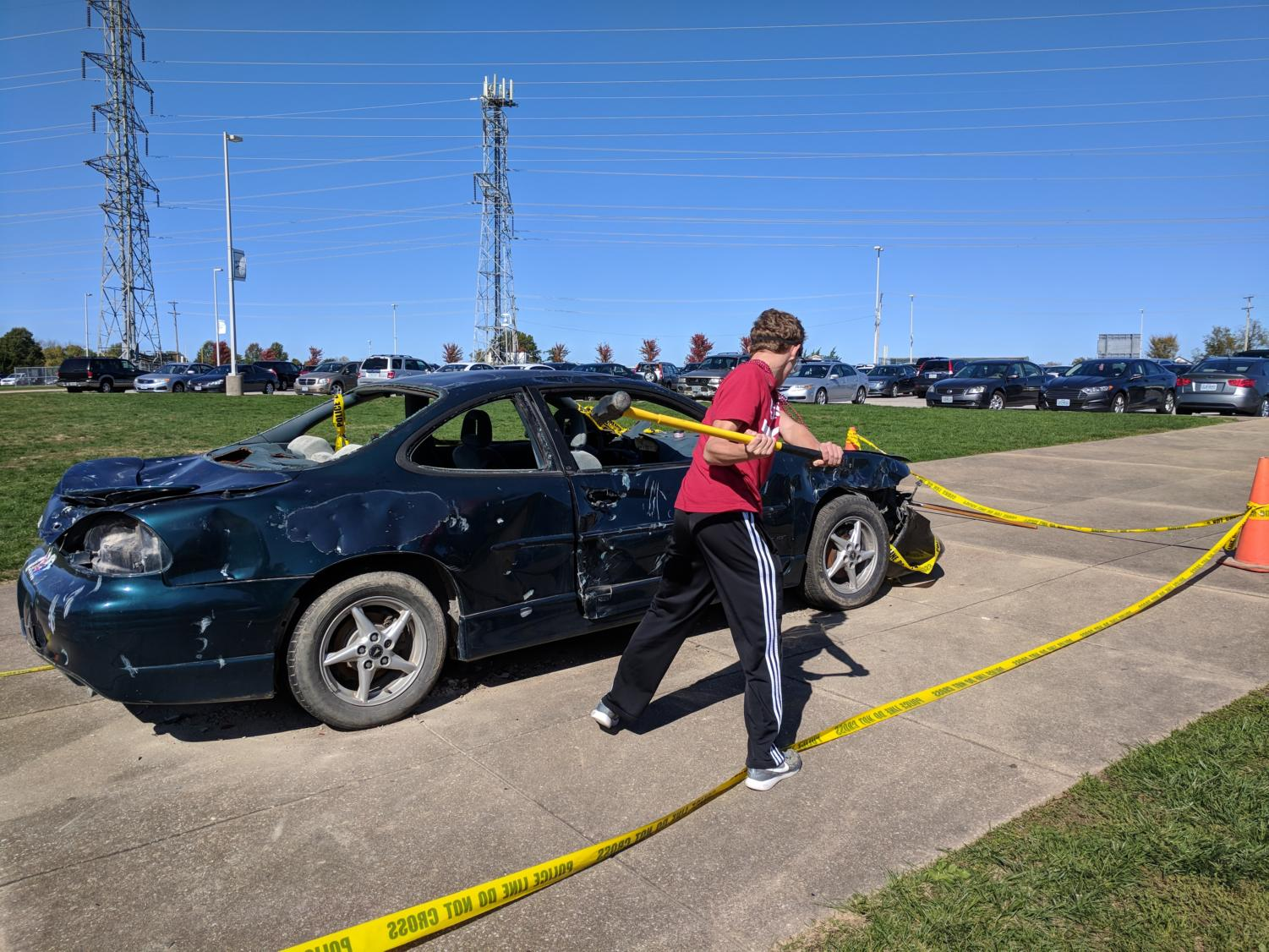 Jackson Estwanick, sophomore, takes a hammer to a decommissioned car for SADD's annual car bash. Estwanick and other students paid one dollar each to take a swing at the car.