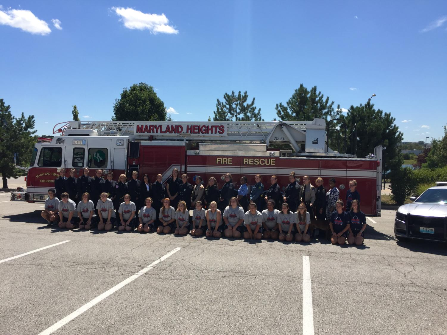 Campers, counselors, and first responders line up in front of a fire truck at the 2017 Camp Fury STL graduation.