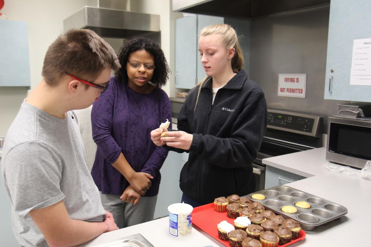 Brendan Morris and Lindsey Scales, juniors, work with Bryah Trenn, junior, to ice cupcakes in their fifth hour Life After High School class.