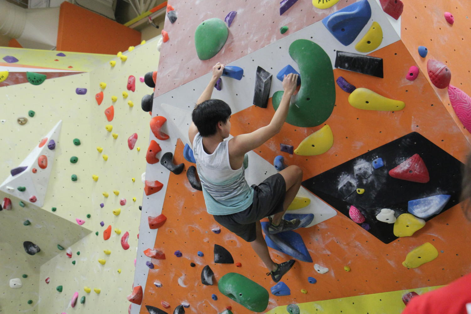 """Jacob Chang, senior, free climbs at practice on Jan. 21. """"I like it because you can see your improvement,"""" Chang said. """"You can see it from your grip strength to your overall strength to get higher and climb harder routes."""""""