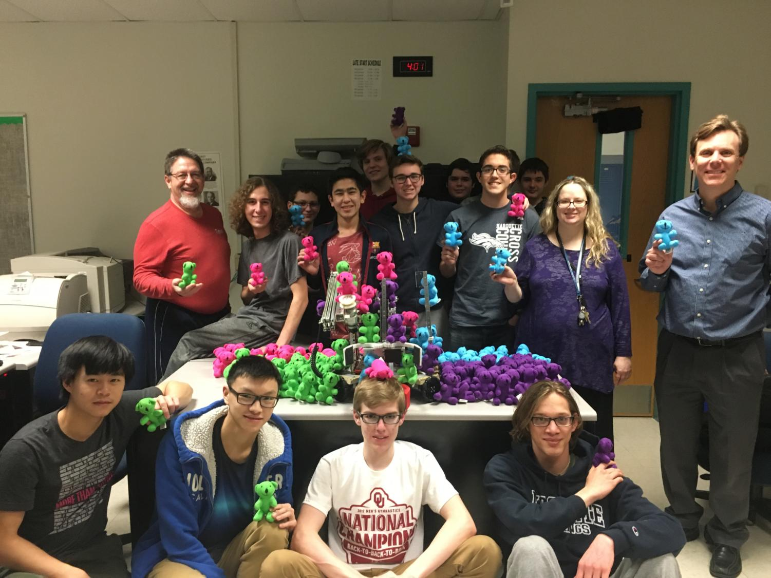 The Baryons Robotics team poses with the gifts that they plan to deliver to patients at Mercy Hospital. The team will be competing at State this weekend.
