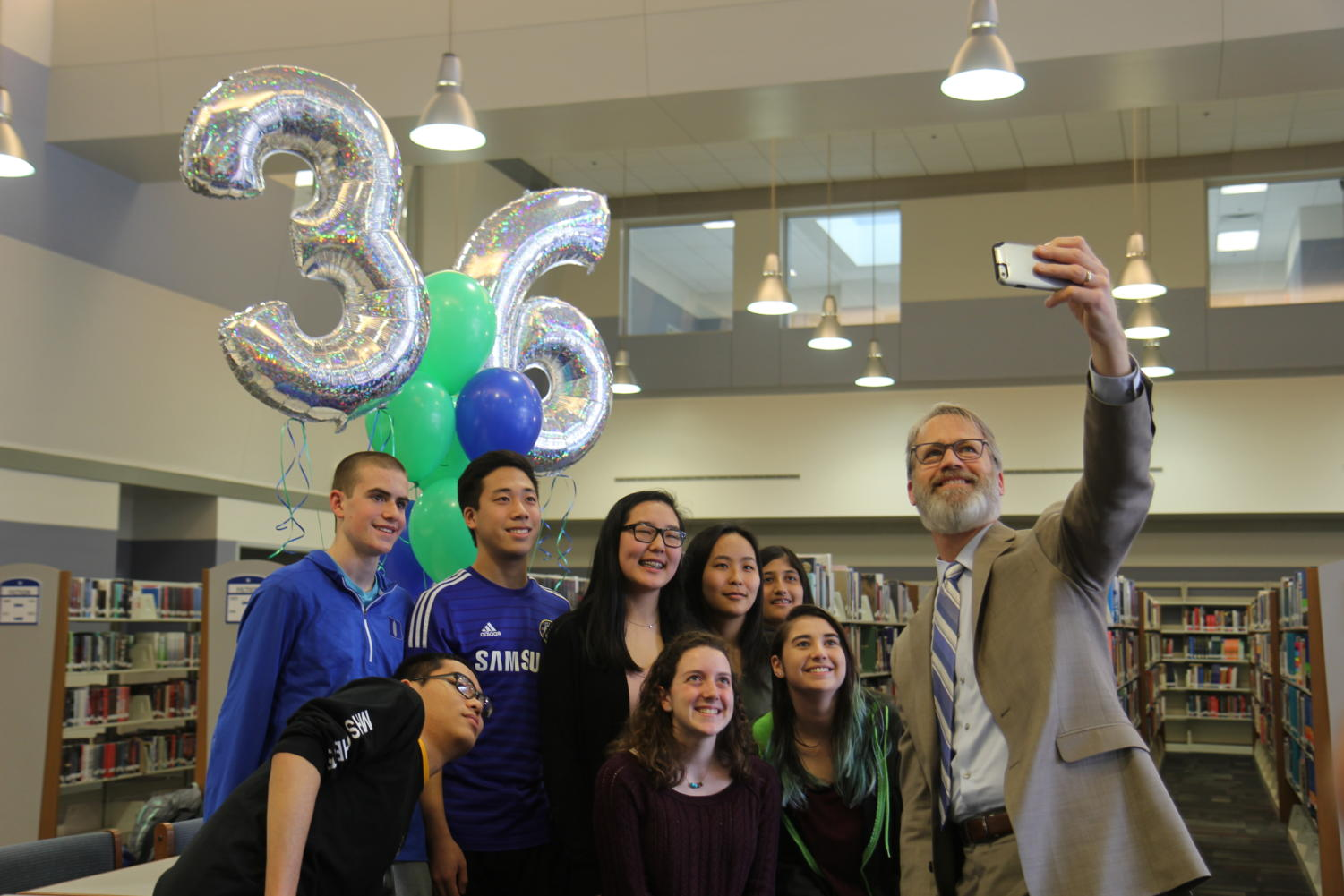 Superintendent Dr. Eric Knost snaps a selfie with the nine students who scored a 36 on the ACT: Jacob Besch, William An, Michelle Li, Rachel Pang, Sriya Kosaraju, Michael Wu, Brooke Davis and Sydney Ring.