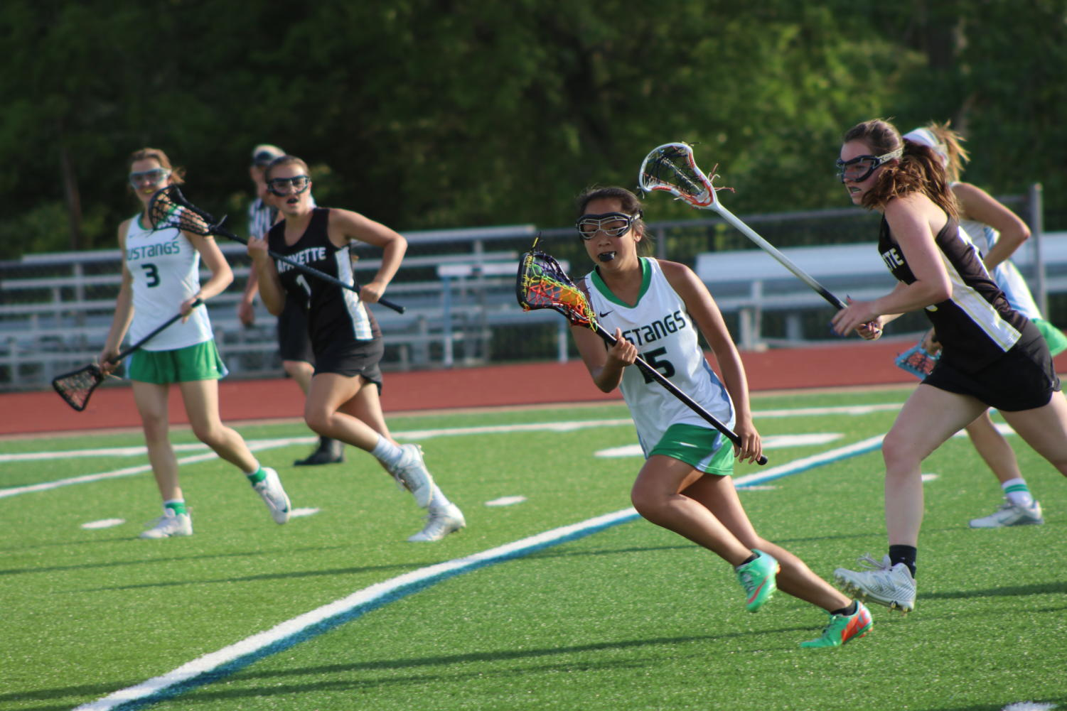 Kailyn Lee, Junior, cradles the ball up to midfield, following an LHS scoring attempt. MHS won this game, 14-9.