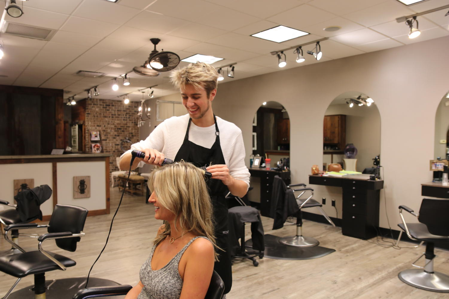 Thomas DeGroot, junior, styles his sister's hair.  DeGroot works as a hairstylist at his mother's hair salon, The Stylist Salon.