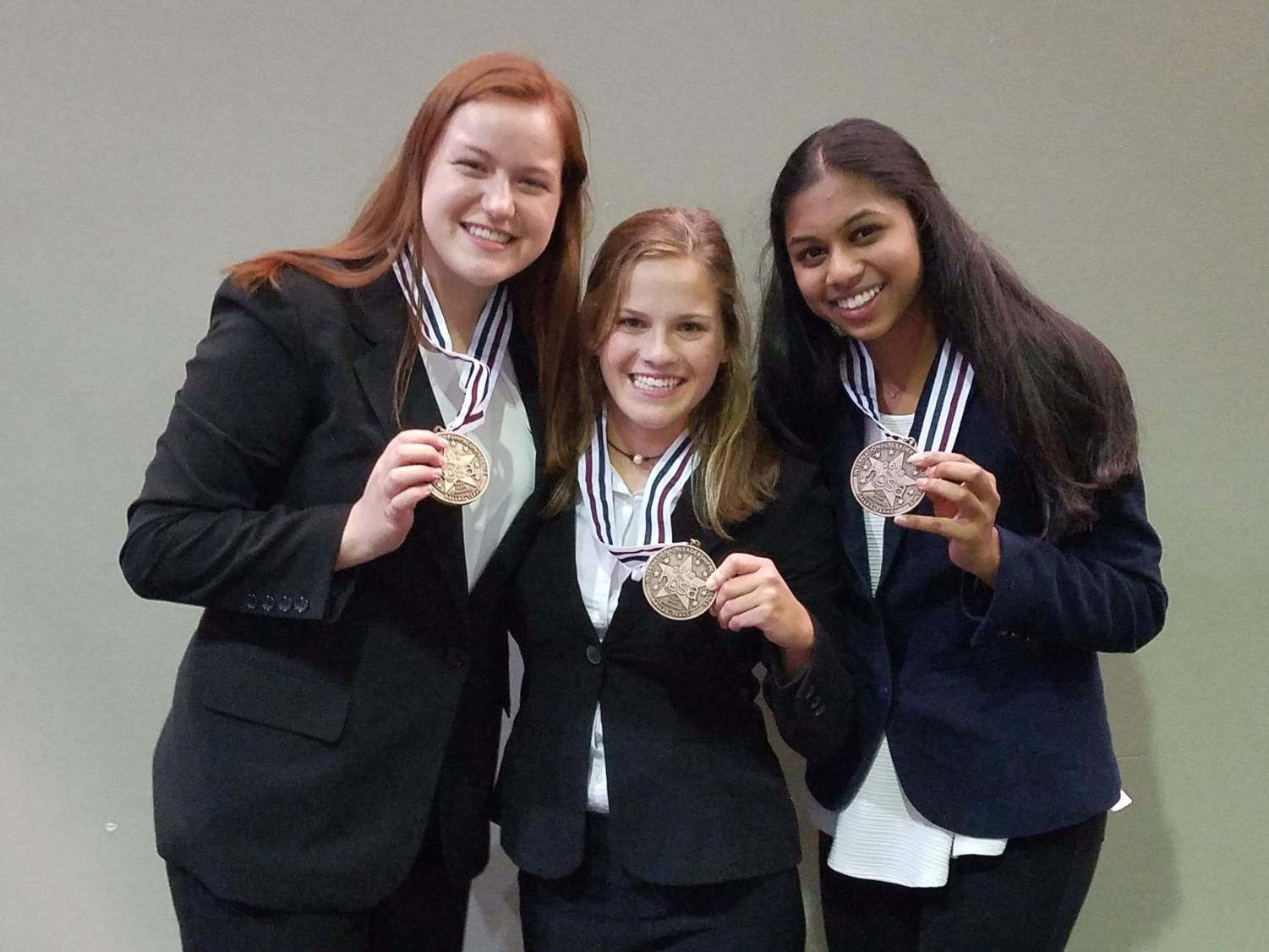 Seniors Kayla Berry, Kelley Sinning and Neha Bollam (from left to right) stand backstage with their medals after learning they placed third for their Tuberculosis Tester.