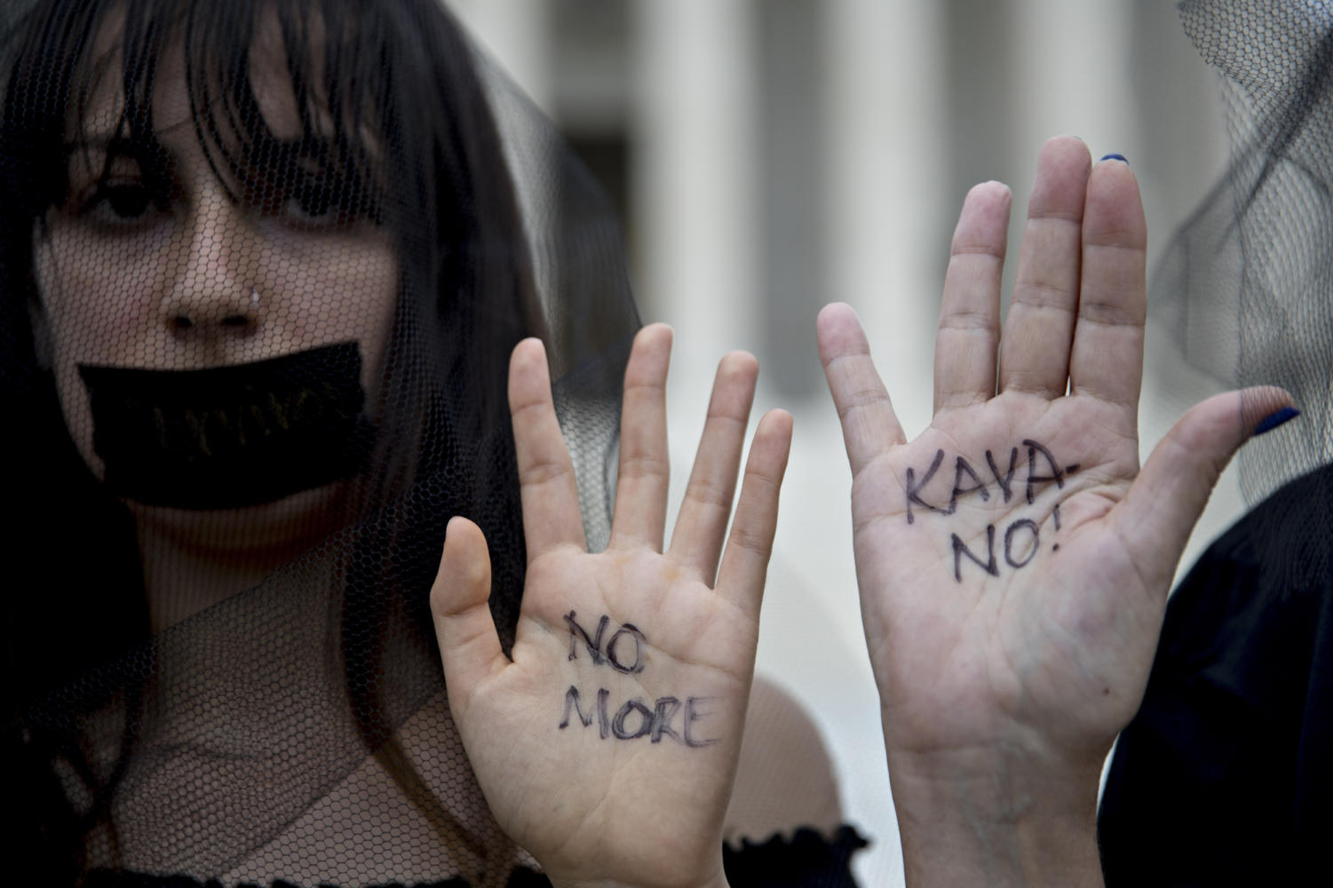 Demonstrators opposed to Supreme Court Associate Justice Brett Kavanaugh stand outside the court with