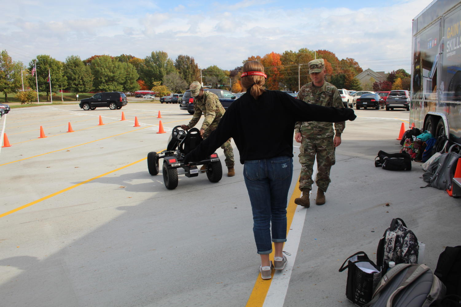 Jilian Bunderson, junior, attempts to walk in a straight line while wearing impairment goggles. She participated in the impaired driving simulations brought to MHS by US Army Staff Sergeants.