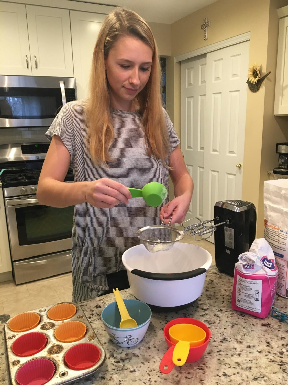 Katie Curran, junior, sifts flour in order to prepare her ingredients. Curran began procrastibaking freshman year in order to deal with the stress of school.