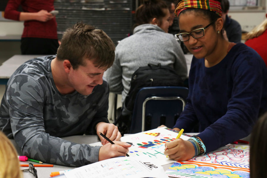 Austin Combs, senior, laughs with his mentor Mary Olubogun, junior, as he draws on his folder during Art Fundamentals.