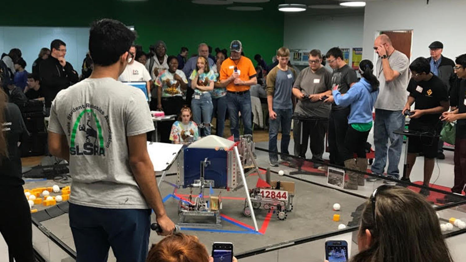 """Arjun Khorana, junior, observes the other robots at the Girl Scouts of Eastern Missouri Meet on Nov. 17. While the Gluons did not participate in this meet, the Lexons placed first and the Barrons placed second. """"It's important to understand how far we've come and it's good to learn from this experience,"""" Khorana said."""