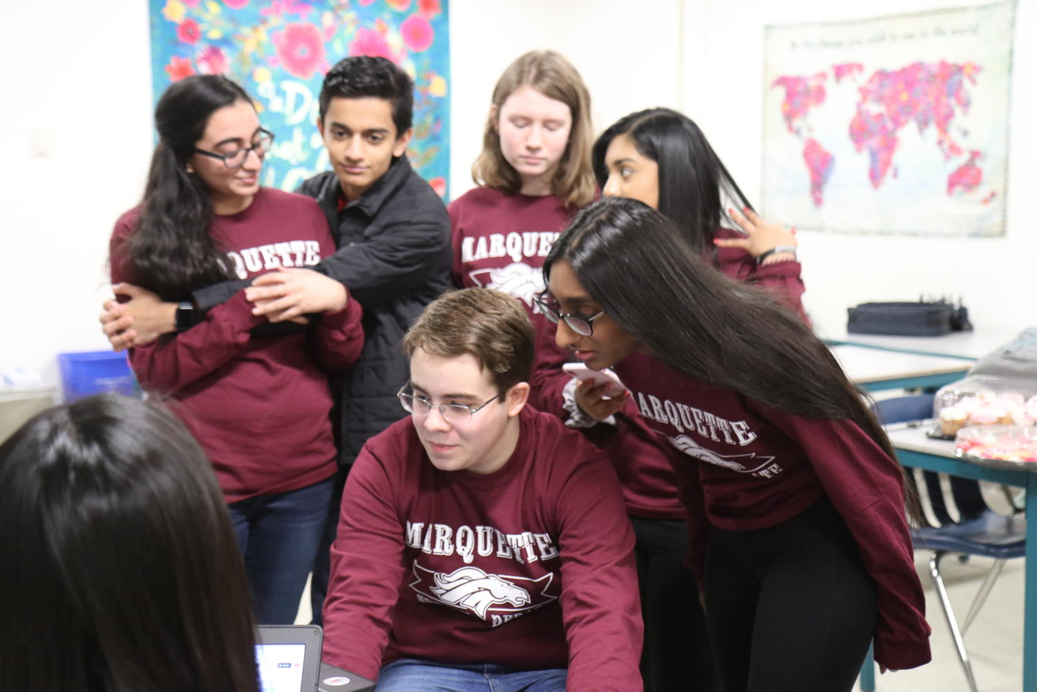 "(Front right) Shruti Punnachalil, junior, works during fourth hour to contact all 904 judges to tell them that the 2019 Marquette Speech and Debate tournament is cancelled due to weather. Punnachalil said many of the judges were members of the MHS community, who would also be affected by the weather. ""Our parents donate a lot of their time, a lot of my family friends have too,"" Punnachalil said. ""The communities also tend to know when the Marquette tournament is, and it's a really great place for people to see each other because they all tend to reunite at our tournament."""