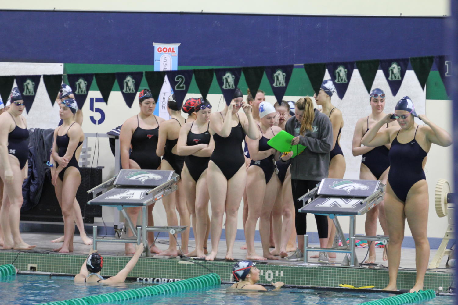 While+Lauren+Berning%2C+senior%2C+prepares+to+swim+a+100-meter+back%2C+Abby+Bomball%2C+junior%2C+shares+the+heat+sheet+of+upcoming+events+with+the+team.+Bomball+was+unable+to+participate+in+this+final+meet+due+to+a+shoulder+injury.+%0A