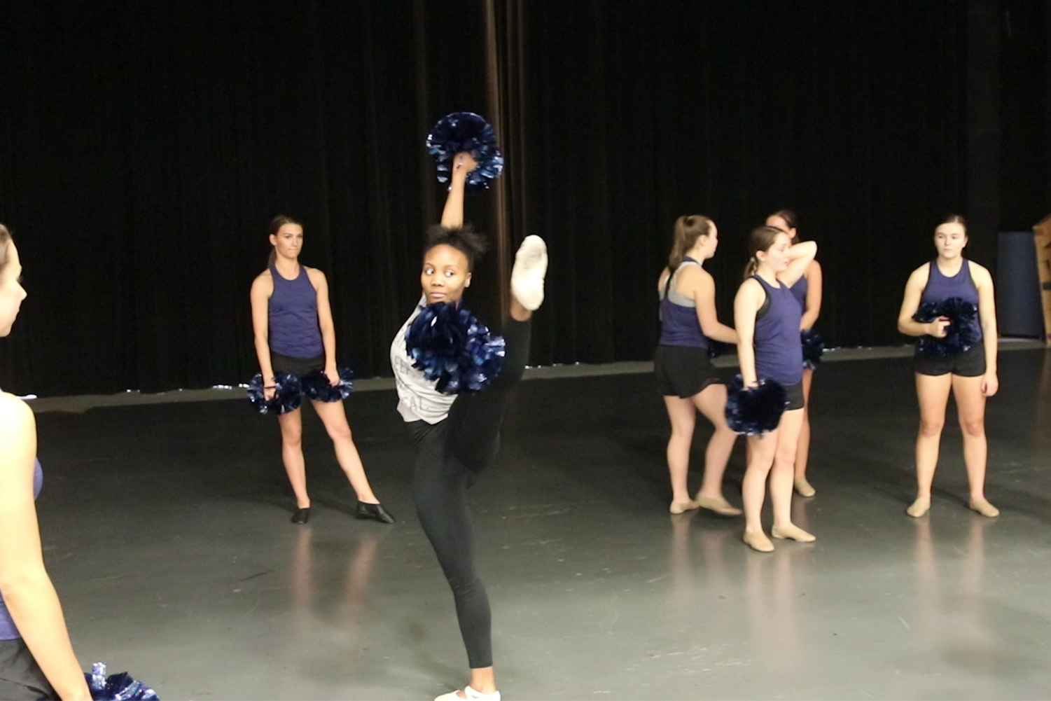 Sam Hall, sophomore, performs a battement with poms. Hall is a ballet dancer who spent a day with the MHS poms team to experience a style of dance foreign to her.