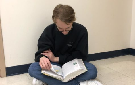 "Grant Hays, sophomore, reads his AP World textbook in preparation for the day's class. Hays said he has about thirty minutes to one hour of homework for AP World a night. ""Keeping up with reading assignments is really important and it makes the class more manageable,"" Hays said. ""You can always rely on your notes if you ever get behind."""
