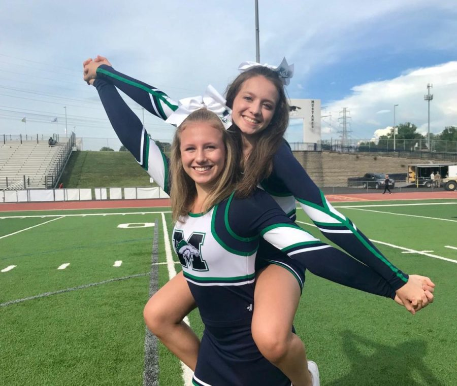 Abby Kaber, junior, poses with Melody Hollenbeck, senior, in their MHS cheer uniforms. Kaber is a part of the MHS varsity cheer team.