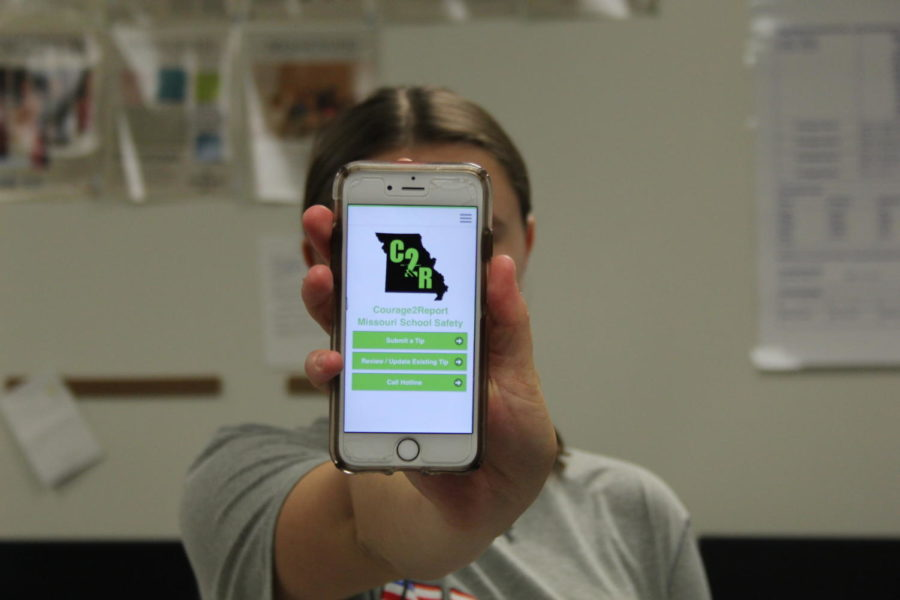 Sarah Harris, senior, holds up a picture of Courage2Report, an app. This app helps bring awareness to school shootings in a timely manner.