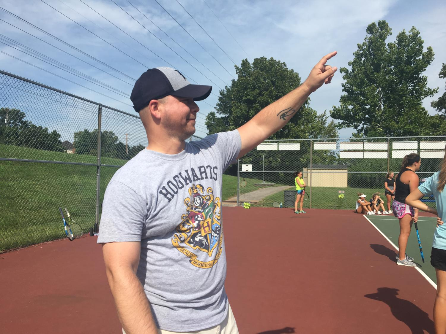 Joshua Hyde, history teacher, leads the j.v. girls tennis team in a series of drills prior to practice. He has become a co-coach of the girls' tennis team this year with Alex Nelle, history teacher.