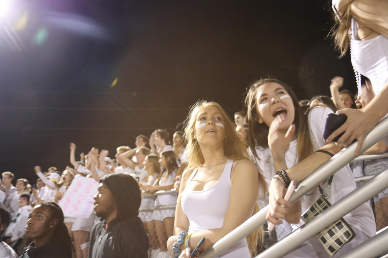 Kenzie+Simmons%2C+senior%2C+watches+the+game+dressed+in+white+as+per+the+game%E2%80%99s+white+out+theme+with+her+friend+Jordan+Boschen%2C+senior.+Simmons+attends+most+football+games.+%E2%80%9CI+thought+the+game+was+a+great+bonding+experience+for+our+grade+because+it%E2%80%99s+somewhere+we+all+come+together+and+all+cheer+for+the+same+thing+on+a+team%2C%E2%80%9D+Simmons+said.+