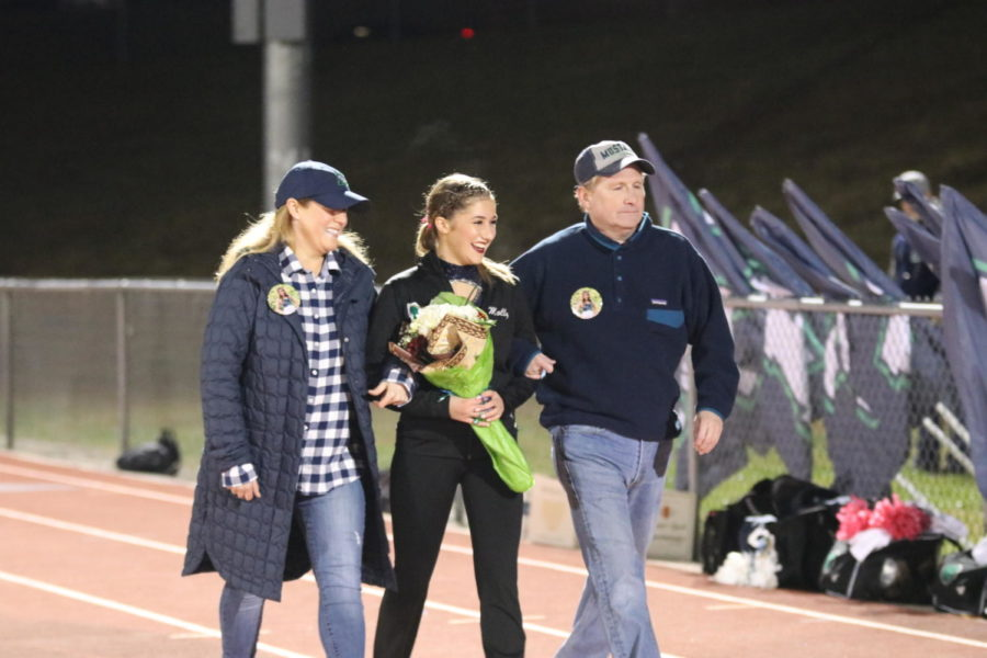 Molly Johnson, senior, walks the track alongside her parents. Mystique, Marching Band, and Cheerleading were all honored during half time.