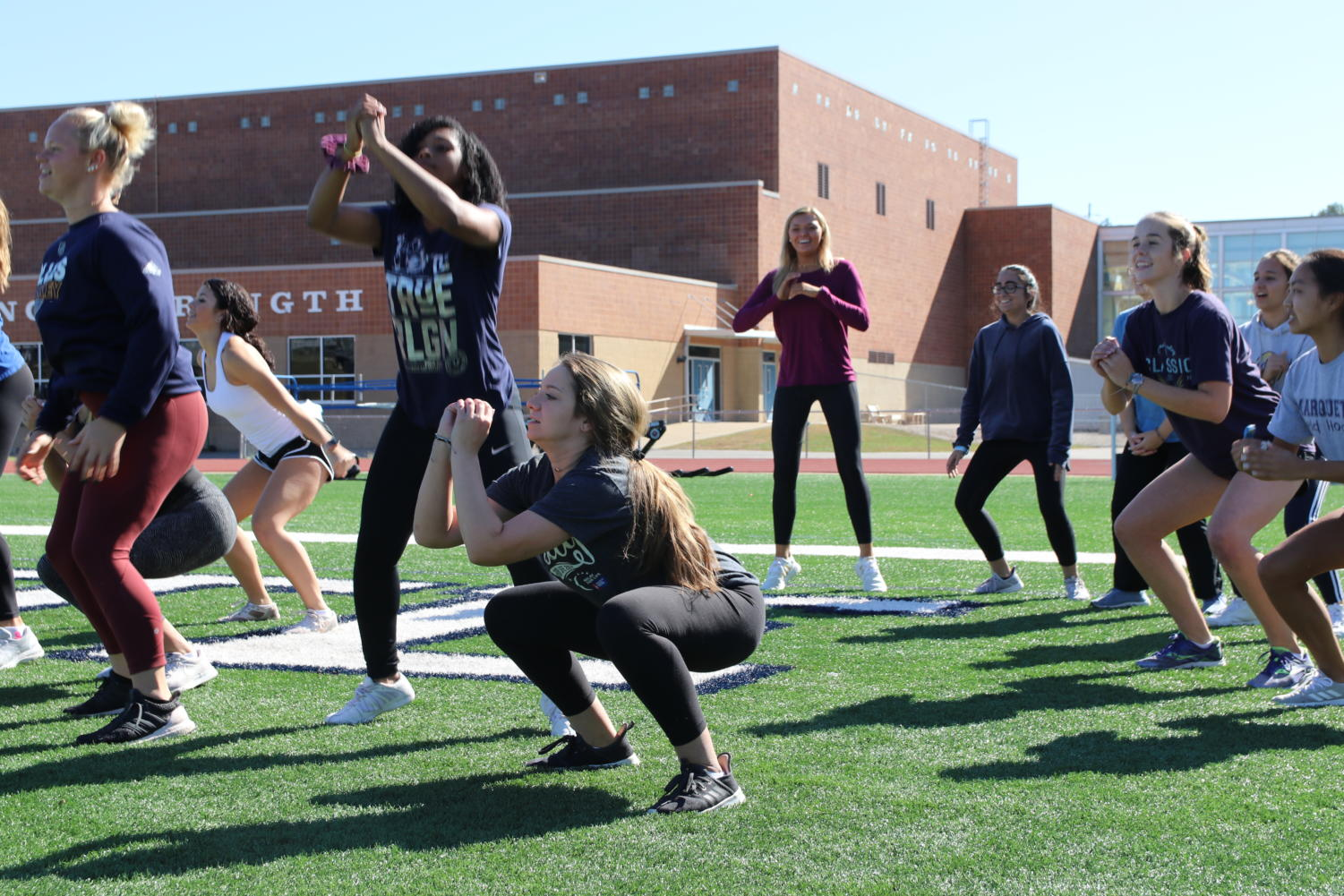 (Center) Melody Hollenbeck, senior, lands after doing a jump squat during Advanced Strength Training. Hollenbeck took the course after being encouraged by her cheer coaches.