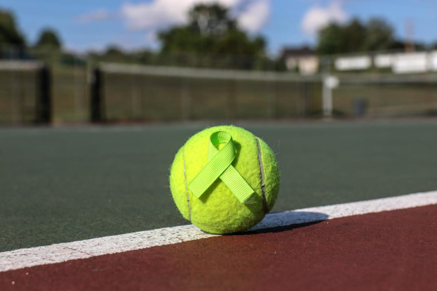 A tennis ball lies on the MHS tennis courts, adorned with a lime green ribbon that represents mental health awareness. Members of the MHS chapter of the National Alliance on Mental Illness (NAMI) distributed the ribbons to teachers, along with flyers informing readers on national suicide prevention month, recognized in September.