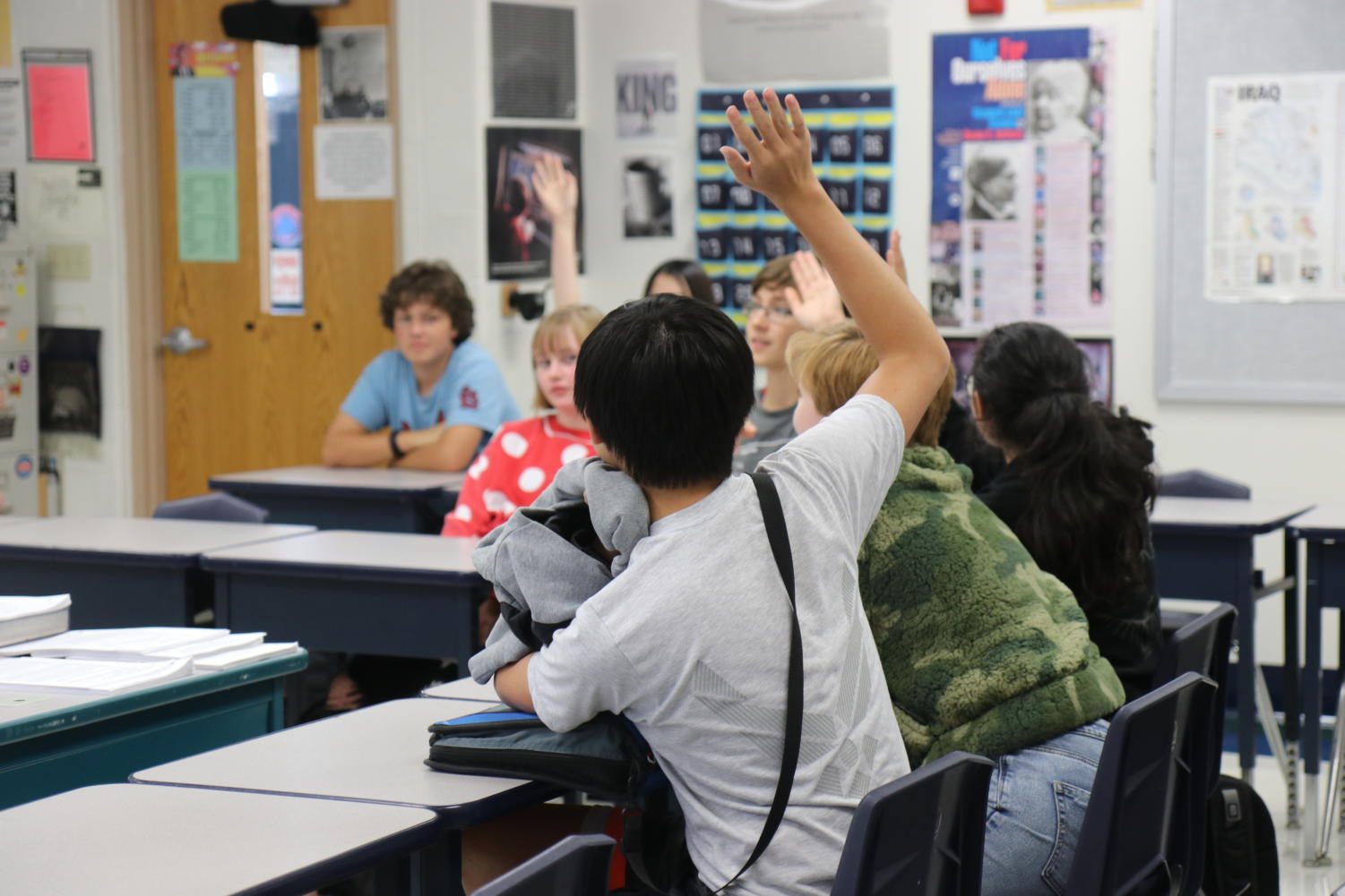 Students raise their hands to vote for the music they will listen to during the next session.