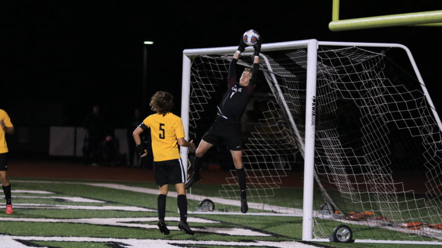 Senior Carson Campbell, goalie, leaps into the air to catch a high center shot. Campbell played without substitution for 80 minutes.