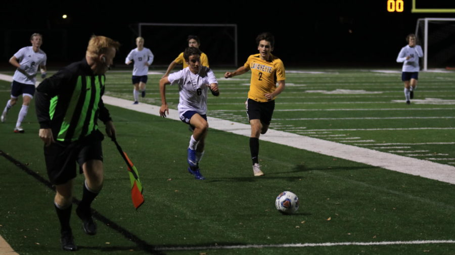 Junior Jake Embleton, right wing, charges up the sideline, attempting to make a comeback after a Lancer goal at three minutes, seven seconds into the first half.
