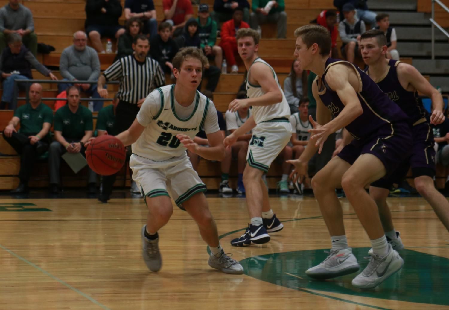 Cole Petch, junior, prepares to pass the ball off during the team's game against Troy Buchanan. Petch shot 3 for 3 and scored 8 points in that game.