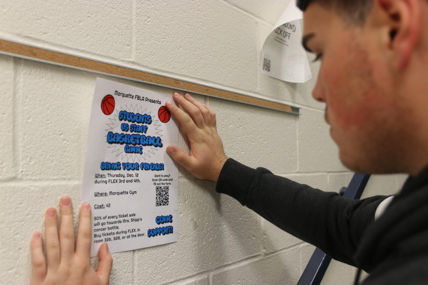Anthony Cova, senior, hangs up a poster for the upcoming student-versus-teacher basketball fundraiser in the main stairwell. In addition to creating posters, Cova has organized teams of students who will help create a commercial, sell tickets, set-up and clean the event and more.
