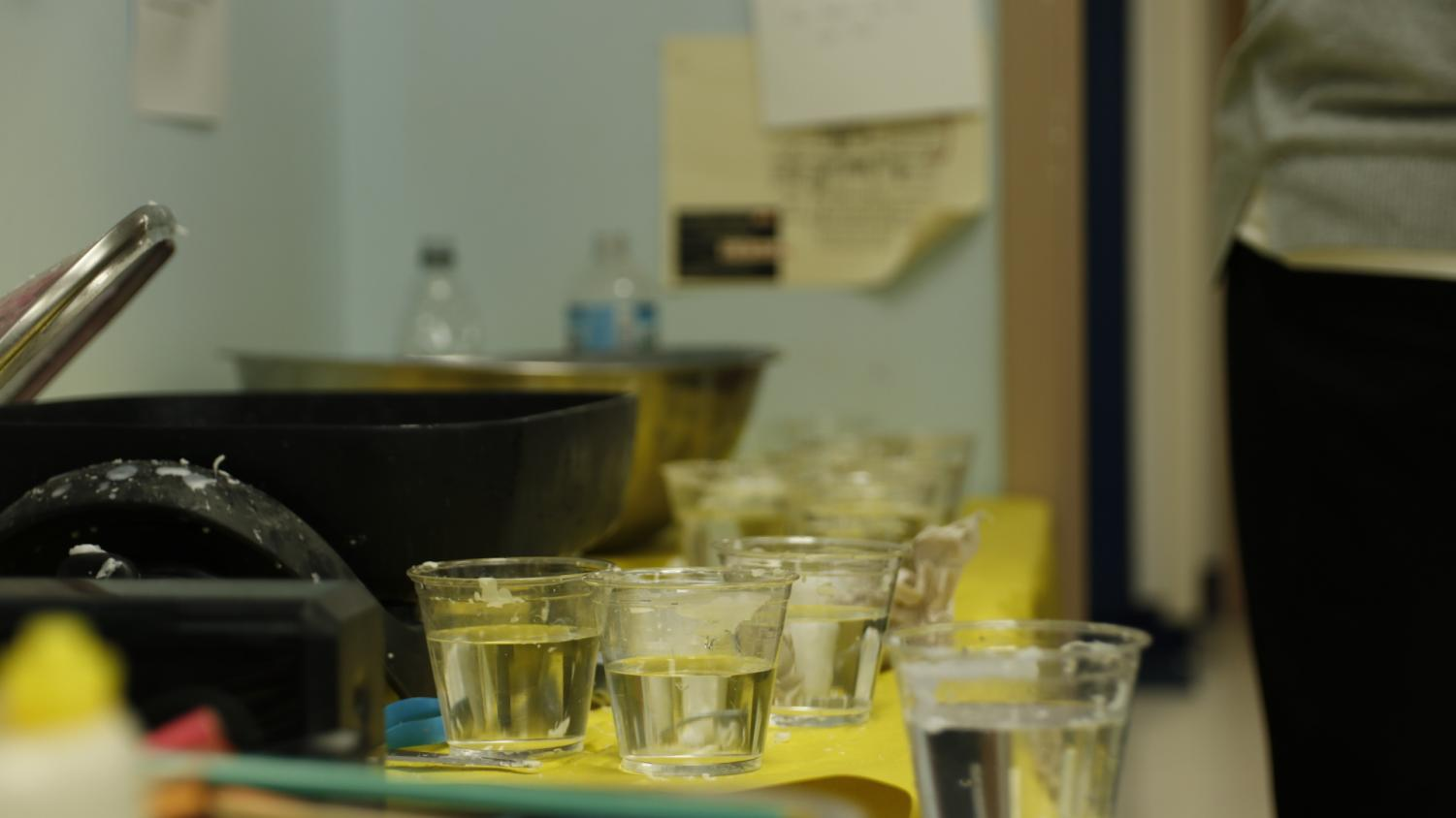 A+row+of+cups+filled+with+cold+water+sit+next+to+a+tray+of+warm+wax.+Students+took+a+ladle+of+hot+wax+out+of+the+tray+and+then+poured+it+into+the+cups%2C+incorporating+the+change+in+temperature+and+the+speed+of+the+pour+to+make+a+shape.+After+they+removed+the+wax+from+the+cup%2C+they+returned+to+their+seats+and+used+a+packet+filled+with+German+words+to+decide+what+shape+their+wax+formed.%0A