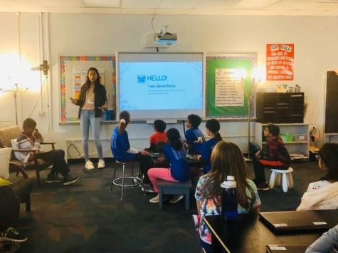 "Janvi Huria, junior, introduces herself to a classroom full of fifth graders. Each unit, Huria comes in for a week to teach fifth graders about additional topics outside their curriculum. ""I hope the kids learn not only can you make a career just by asking questions but hopefully they can find something they"