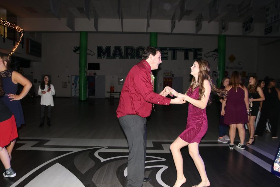 "Juniors Natalie Anderson and AJ Burger dance together. Anderson has attended the dance every year since her freshman year and prefers it to Homecoming because she said there are always fewer people and better music. ""I just go because she goes,"" Burger said."