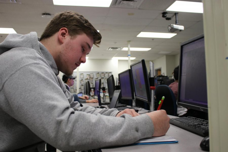 Andy Oitker, junior, tries to stay focused while he works on an in-class assignment. Trying to stay afloat after his parents divorce, he said he has become more mature and independent, often doing his homework without assistance, completing chores around the house, and making his own meals.
