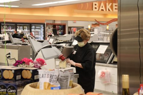Schnucks employee slices meat wearing a mask and gloves.