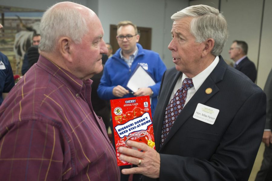 """Missouri Governor Mike Parson hands a packet of Kool-Aid that reads """"Missouri Doesn't Need Stay-At-Home"""" to Agriculture Secretary Sonny Perdue. Parson believes that the disparity between the number of cases in urban areas versus rural areas in Missouri is evidence that a statewide stay-at-home order is unnecessary. Photo illustration by Jackson Estwanick."""