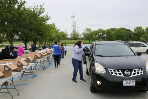 Caps and gown packages are delivered to senior's car windows by MHS staff members wearing masks and gloves.