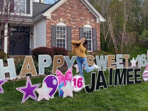 "Jaimee Bunderson, sophomore, stands in front of the birthday lawn signs saying ""Happy Sweet 16 Jaimee."""