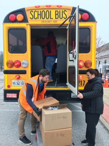 South Base Terminal Manager Alex Gensler (left) and Starr Giammanco, meal distributor, (right) load school buses with boxes of prepared meals for regional distribution.