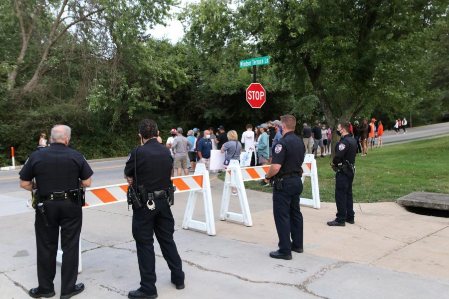 Creve Coeur police officers stand guard at the entrance of County Executive Dr. Sam Page's neighborhood as protesters begin to gather. Police were on site to keep protesters from advancing farther up the street to Dr. Page's home.