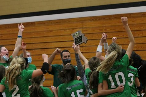 The Mustangs celebrate with the District championship plaque after sweeping the Francis Howell Knights three sets to none. This was their first district championship win since 2013.