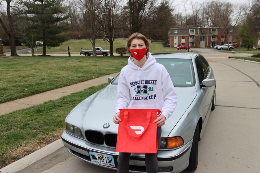 Larson Hill, senior poses with his car, warming bag and mask, all required for his job delivering food for DoorDash. Recently, DoorDash has become a popular employer for MHS students due to it's easy sign up, flexibility and high pay.
