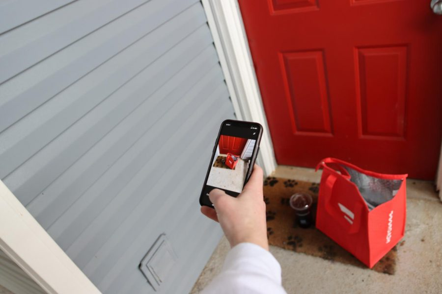 """After arriving at the customer's home, Hill puts the order by the front door and takes a photo of the order to notify the customer it has been delivered. To keep both drivers and customers safe deliveries are done """"contactless"""" where food is left on customer's doorsteps rather than being delivered face to face."""